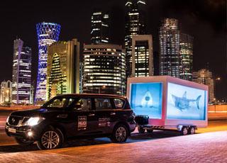 """""""بالصور"""" سمكة قرش ضخمة تتجول في شوارع مدينة الدوحة في سيارة نيسان"""