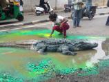 """""""بالصور"""" فنان هندي يضع تمساحاً ضخماً في حفرة بالمدينة لتنبيه المسؤولين حتى يشاهدونها"""