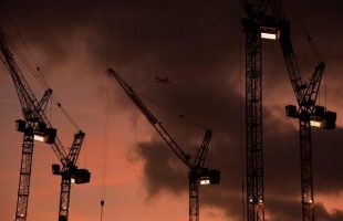 A plane flies behind cranes standing on construction sites, at dusk in London, December 9, 2013. REUTERS/Toby Melville/File Photo